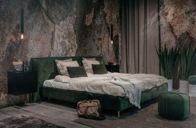duże zielone łóżko na tle ścian z kamienia
