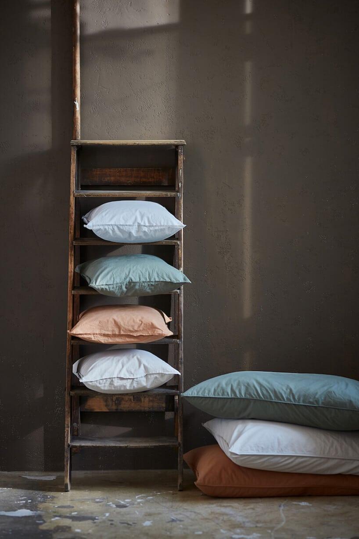 wysoka szafka zpułkami oraz na nich kolorowe poduszki wróżnych kolorach