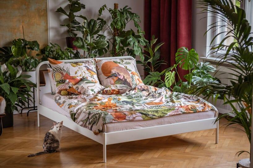 łóżko zbiała ramą oraz kolorowymi wzorami na pościeli oraz poduszkach wsypialni zzielonymi kwiatami przy ścianie