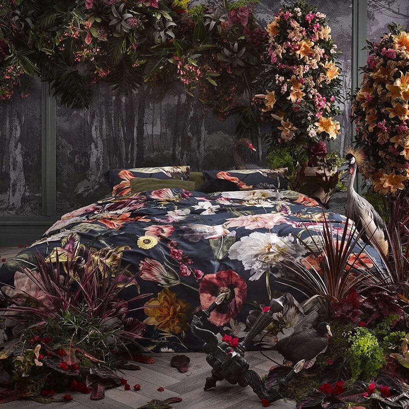 kwiecisty bukiet na ścianie wkolorach szarych desek przy łóżku kolorową pościelą
