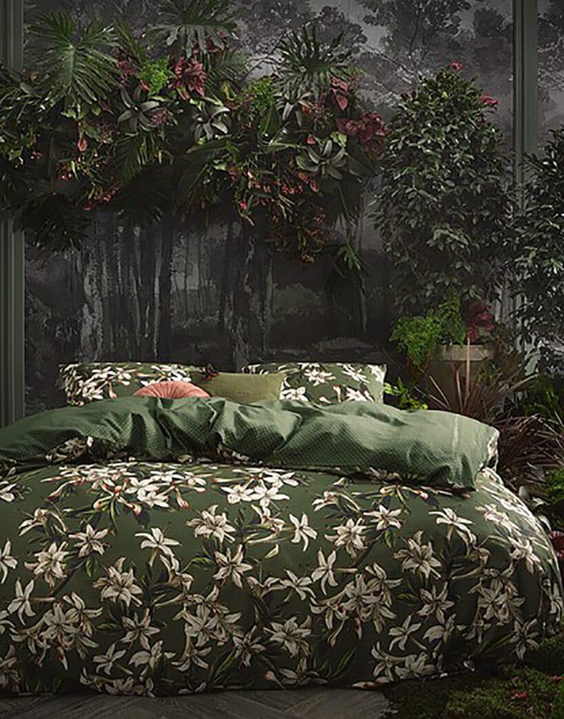 las tropikalny wsypialni przy łóżku zpościelą wkolorze ciemnej zieli oraz białych kwiatów