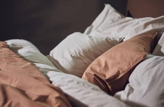 adwie pościele w kolorach białym oraz brązowym na łóżku wraz poduszkami