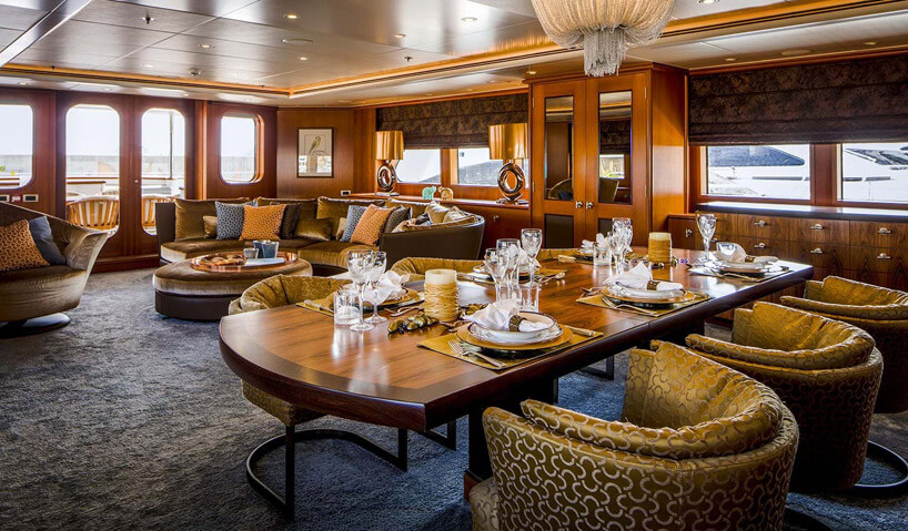 złotawe półokrągłe fotele wdużym pomieszczeniu na wodzie