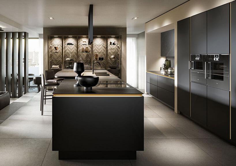 duża elegancka kuchni zczarnymi matowymi szafkami idużą wyspą ze złotymi akcentami