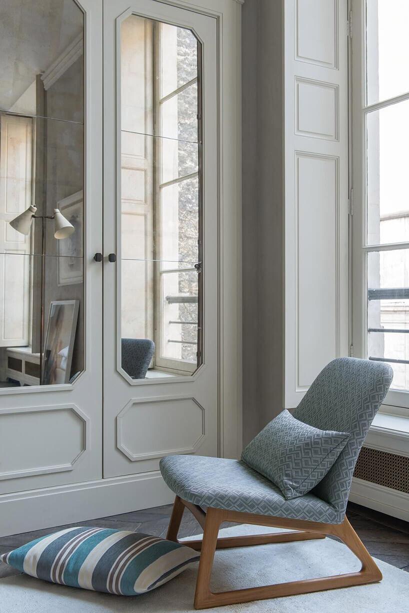 niebieski fotel na tle starych białych drzwi