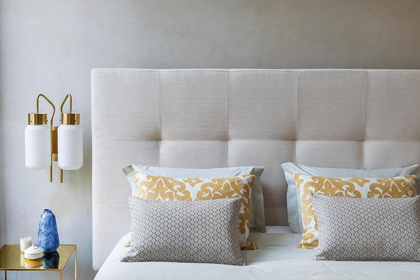 białe poduszki ze złotymi wzorami na łóżku