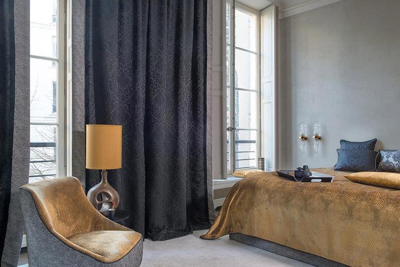 sypialnia zdużym łóżkiem idługimi zasłonami