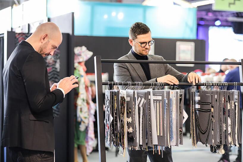 dwóch mężczyzny przeglądających dodatki do ubrań