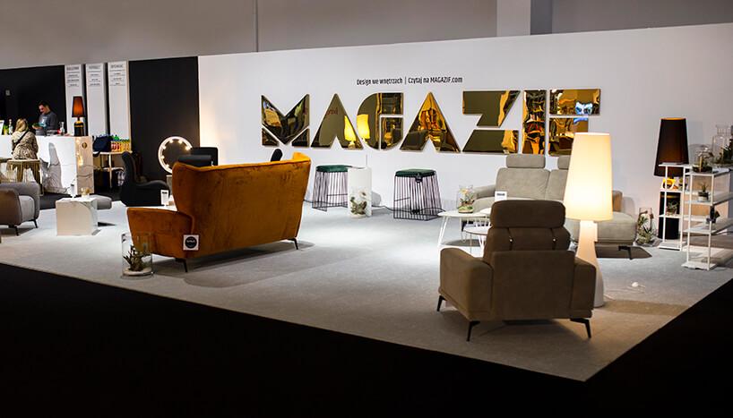 stoisko MAGAZIF na Warsaw Home 2019 pomarańczowa sofa iżółty fotel na tle błyszczącego złotego napisu MAGAZIF