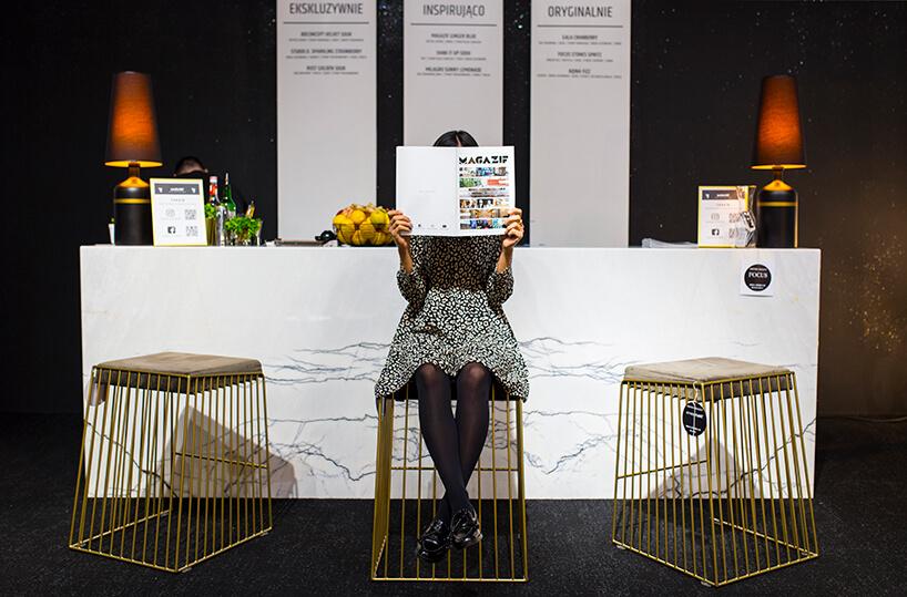 stoisko MAGAZIF na Warsaw Home 2019 kobieta wbiało czarnej sukience czytająca broszurę MAGAZIF na tle baru