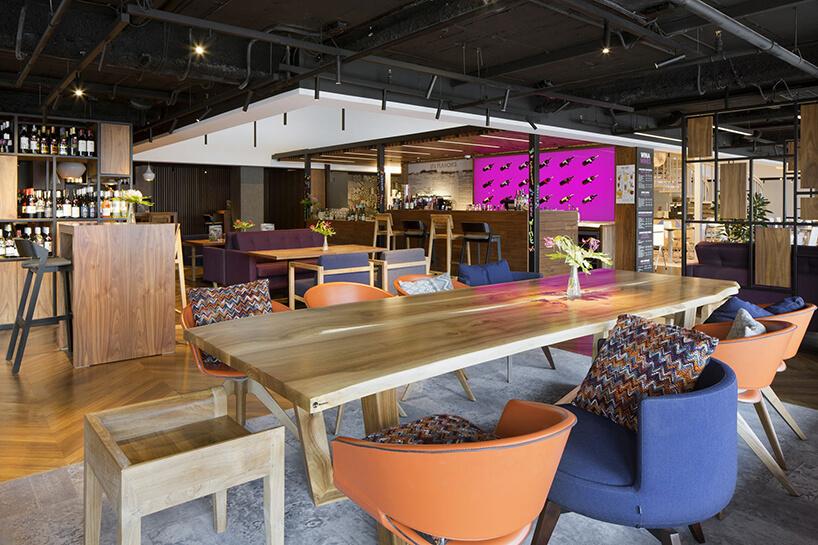 wnętrze hotelu Novotel Poznan Centrum duży drewniany stół zróżnymi krzesłąmi na tle małego drewnianego baru