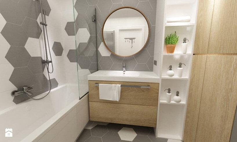 mała łazienka zwanną umywalką iokrągłym lusterm