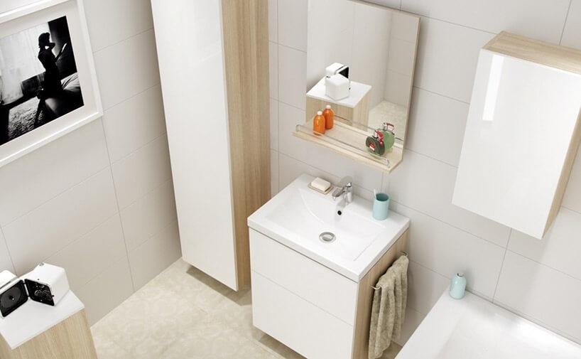 mała beżowa łazienka zbiałymi frontami idrewnianymi szafkami