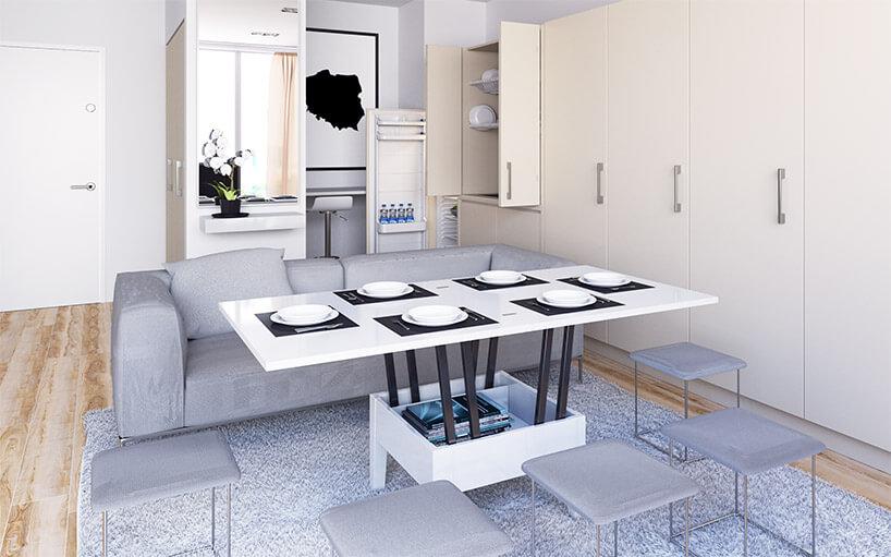 jasny salon zrozłożonym małym białym stolikiem rozkładanym wwyższy stół