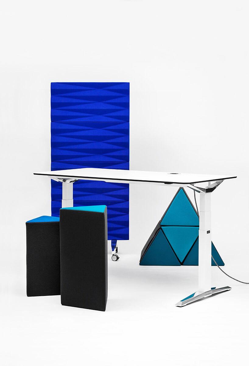 białe biurko obok geometrycznych siedzisk iniebieskiej ścianki