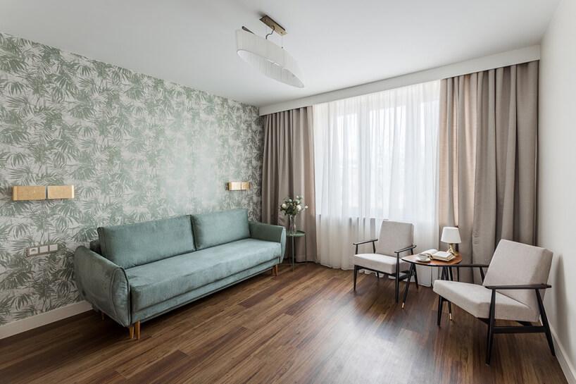 mały salon zciemną podłogą zzieloną sofą dwoma białymi fotelami