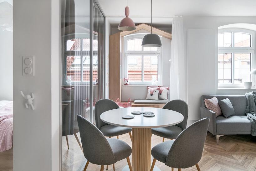 biały stolik zczterema szarymi krzesłami na tle okna
