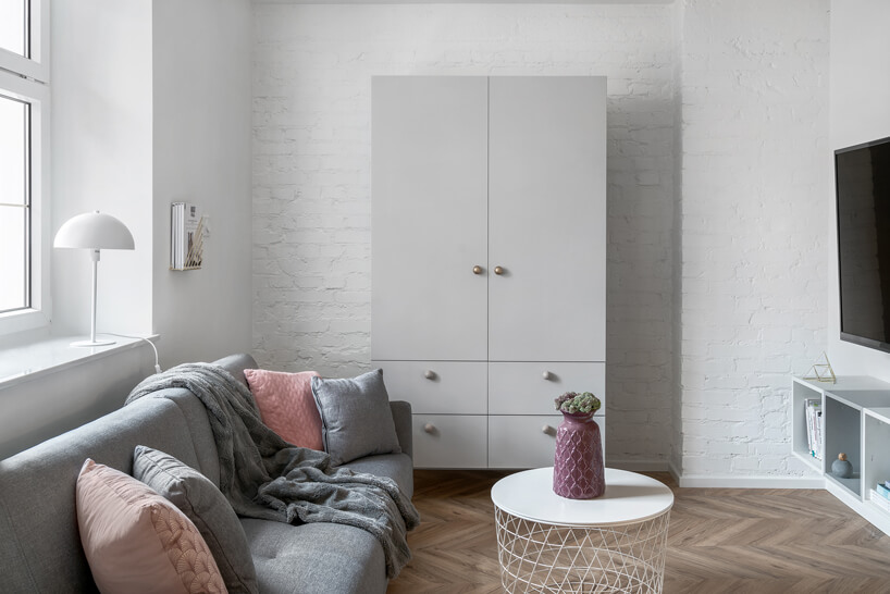 mały biały stolik przed szarą sofą na tle wolnostojącej szarej szafy