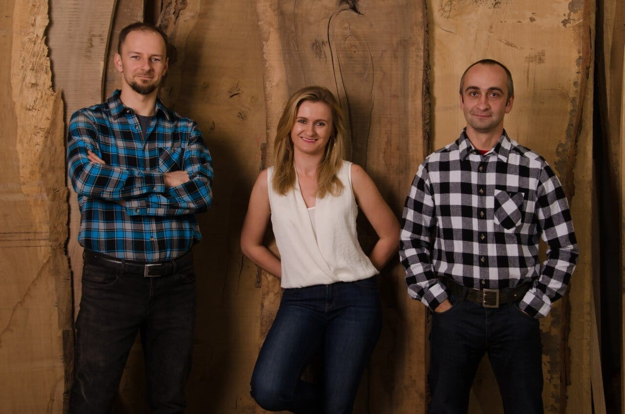 trzy osoby stojące koło siiebie na drewnianym tle - dwóch mężczyzn iwśrodku kobieta