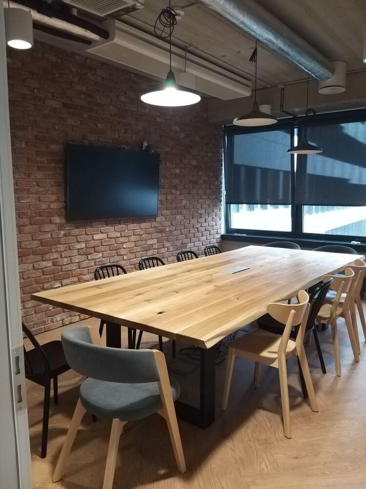 drewniany duży stół zkrzesłami wsali konferencyjnej