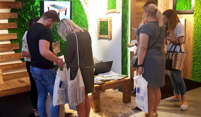 grupa odwiedzających przy targowym stoisku obrazami zmchu
