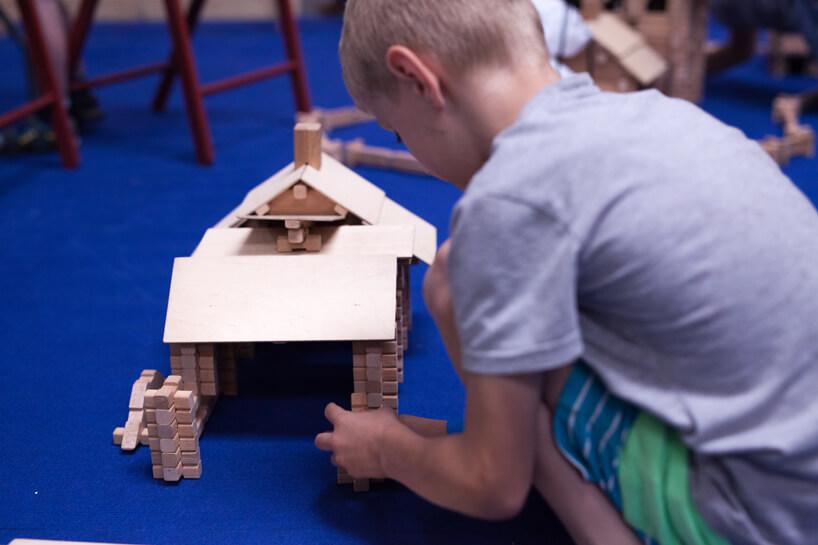 chłopiec budujący dom zdrewnianych klocków na niebieskiej wykładzinie