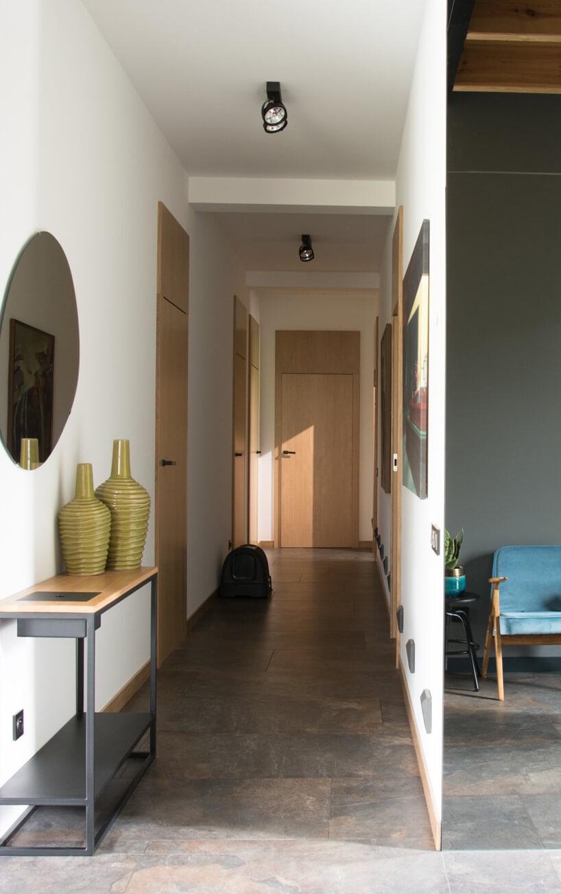wąski biały przedpokój zdrewnianymi drzwiami iciemną podłoga zmotywem kamiennym