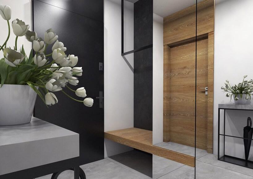projekt jasnego przedpokoju zcuemnymi drzwiami wejściowymi iszafą schowaną za lustrem