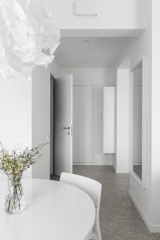 cały biały przedpokój zdużym lustrem na ścianie łączącej zsalonem zbiałym stołem