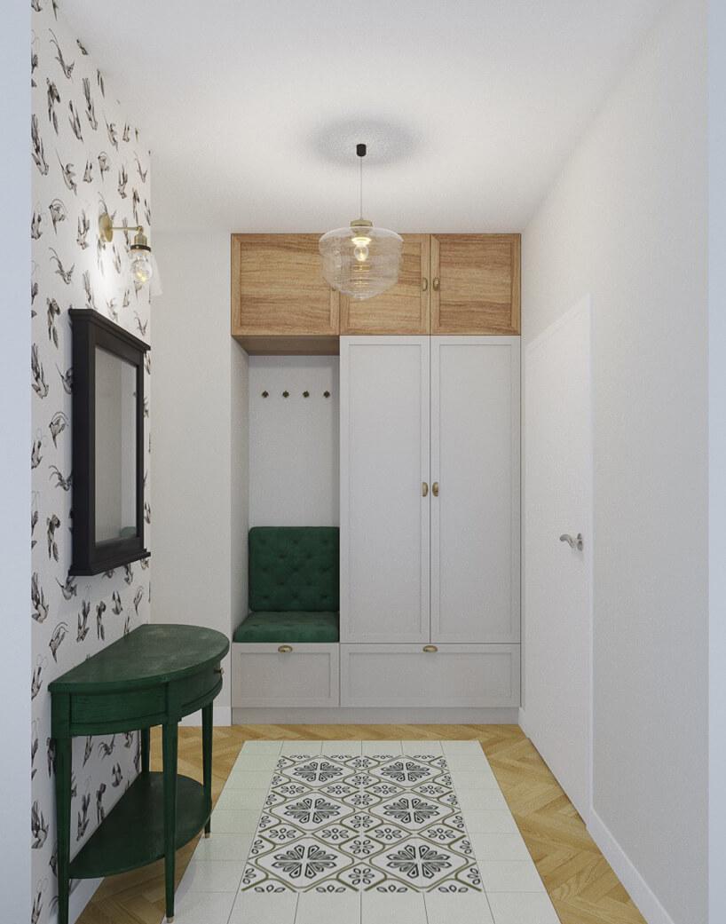 białe wnętrze zjedną ścianą ztapeta wmotyw ptaków zmałym zielonym siedziskiem obok białej szafy