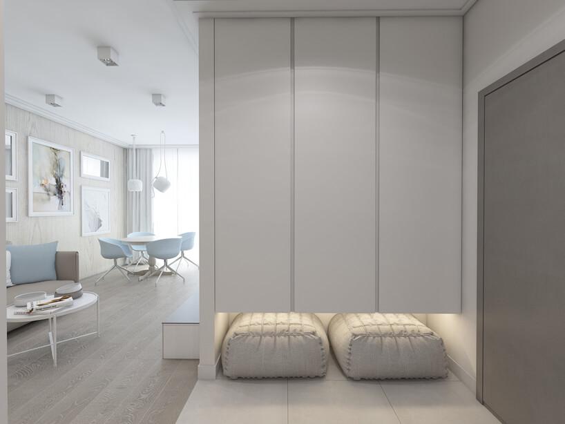 biały mały przedpokój zdużymi kaflami na podłodze zdwoma siedziskami podsuniętymi pod białą szafę