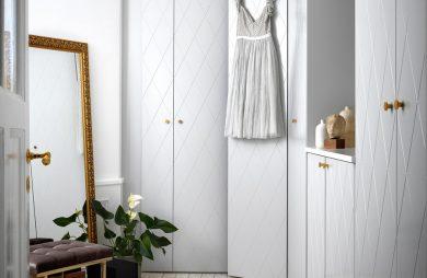 mały przedpokój z biała zabudową ze złotymi uchwytami obok dużego stojącego lustra