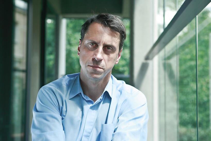 mężczyzna wniebieskiej koszuli na tle szklanych ścian