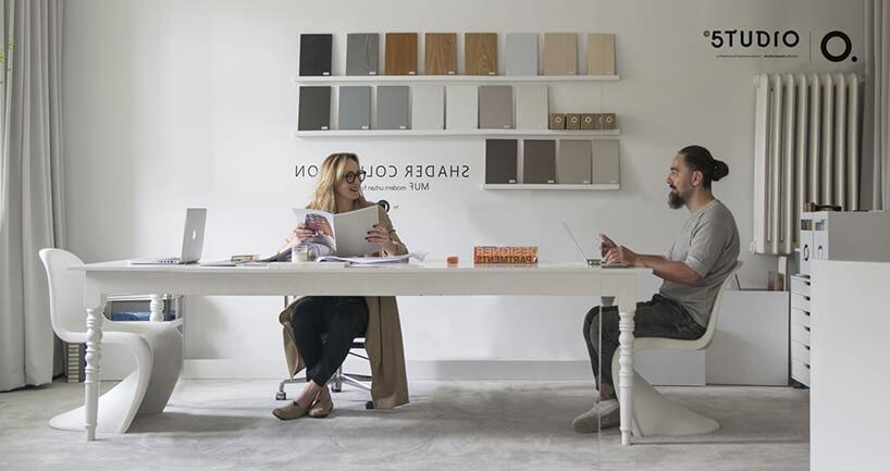 dwie osoby siedzące przy dużym białym biurku wpracowni projektowej