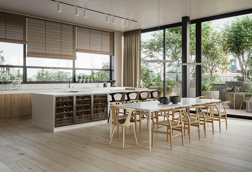 przestronna jasna kuchnia zbiała wyspą oduży biały stół zdrewnianymi krzesłami na tle przeszklonych ścian