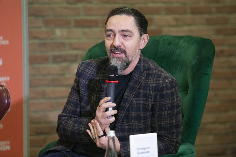 Grzegorz Goworek wkraciastym garniturze mówiący do mikrofonu