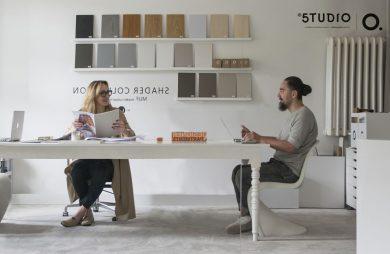 dwie osoby siedzące przy dużym białym biurku w pracowni projektowej
