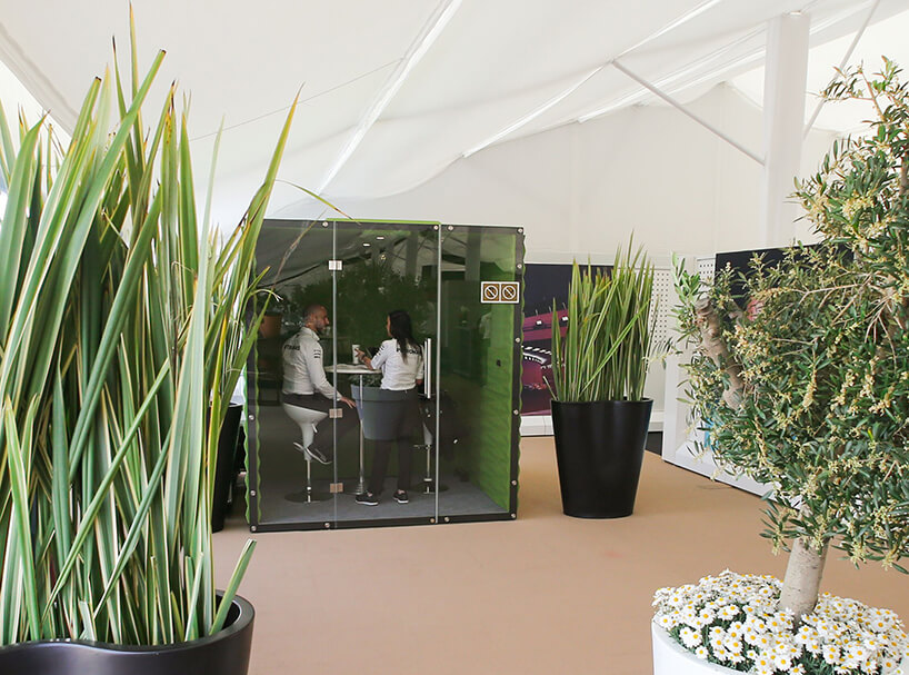 zielony box VANK pośród dużych roślin wdoniczkach zdwoma osobami znapisem PETRONAS na plecach