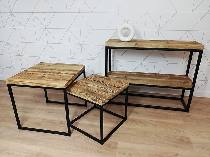 dwa metalowe stoliki zdrewnianymi blatami na tle dwu poziomowej szafki zdrewnianymi półkami