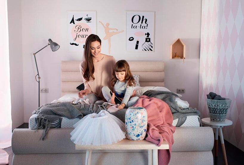 dziewczynka zmamą siedzą na materacu kieszeniowym wsypialni wpastelowych kolorach