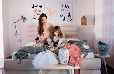 dziewczynka z mamą siedzą na materacu kieszeniowym w sypialni w pastelowych kolorach