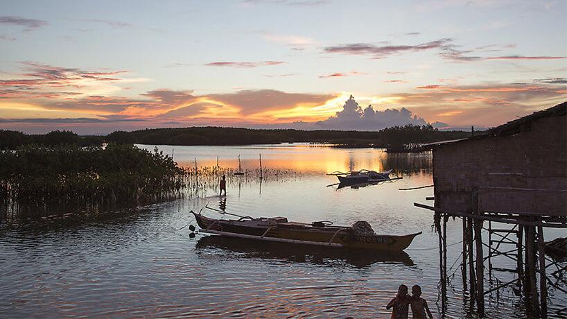 małe łodzie rybackie na jeziorze podczas zachodu słońca