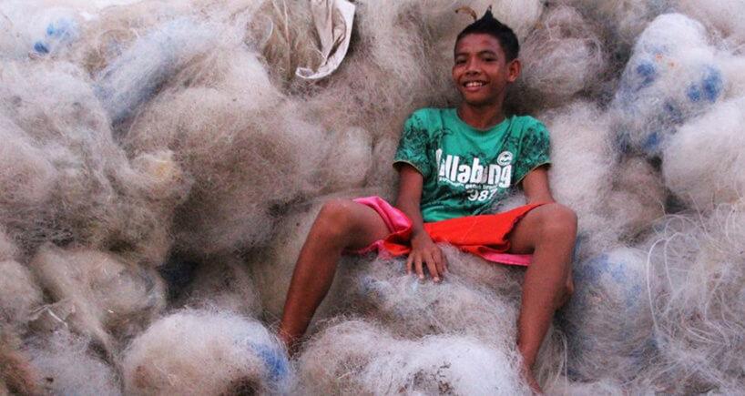 chłopiec leżący na górze starych sieci rybackich