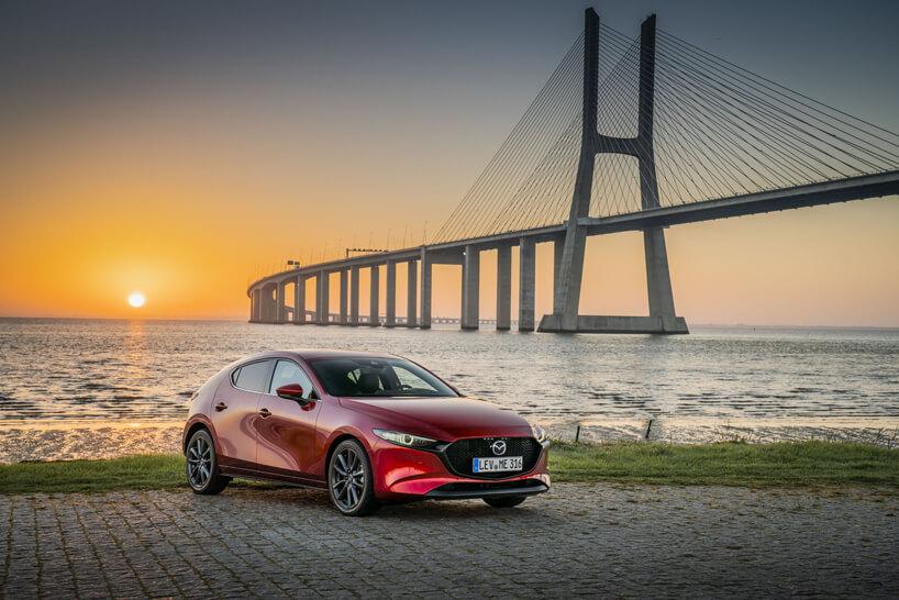 Mazda 3 na tle długiego mostu podczas zachodu słońca