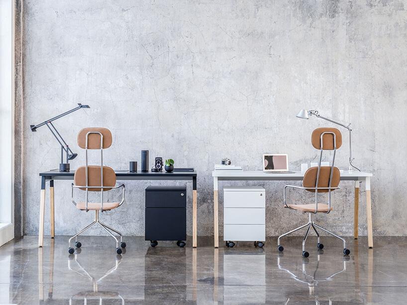 białe iczarne biurko obok siebie waranżacji MDD na tle betonowej ściany wbiurze open space