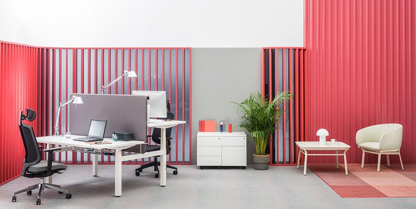 aranżacja pokoju wbiurze zbiałym biurkiem iprzestrzenią do relaksu na tle czerwonych elementów od MDD