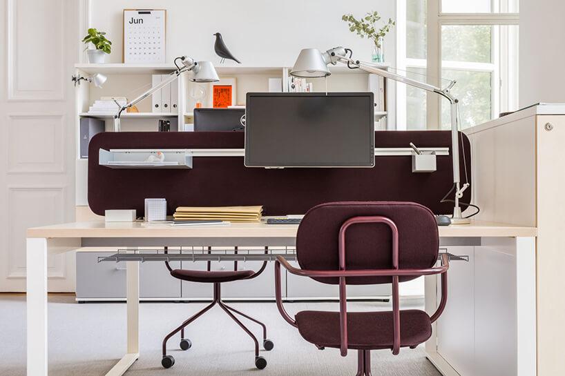 podwójne biurko zciemną ścianką wjasnym biurze