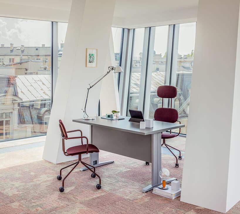 aranżacja pokoju wbiurze od MDD zszarym biurkiem iczerwonymi krzesłami na tle dachów