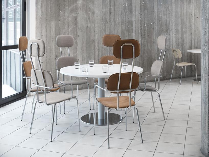 aranżacja przestrzeni socjalnej od MDD zbiałymi okrągłymi stołami iwysokimi krzesłami na tle betonowych ścian wbiurze