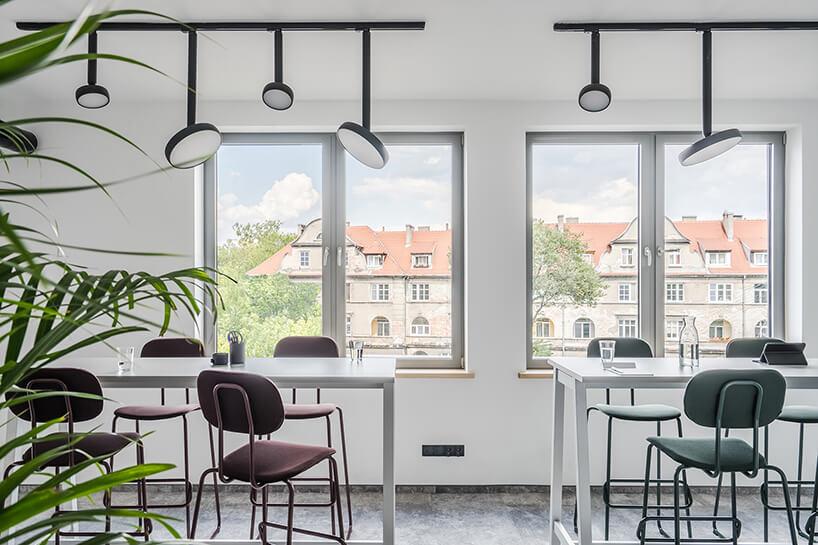 nowoczesna przestrzeń biurowa MDD Work Together białe wyższe biurka zkrzesłami na tle okien zwidokiem na kamienice